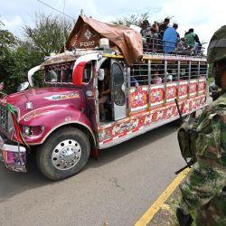 Un autobús pasa junto a los soldados que hacen guardia cerca de una barricada que bloquea la carretera Panamericana luego de una protesta contra el gobierno provocada por un proyecto de reforma tributaria ahora abandonado, en Cali, Colombia.   Foto:Luis Robayo / AFP