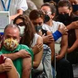 La gente espera luego de recibir dosis de la vacuna Pfizer-BioNTech contra COVID-19 en un centro de vacunación para mayores de 50 años instalado en la Biblioteca Vasconcelos, en la Ciudad de México.   Foto:Pedro Pardo / AFP