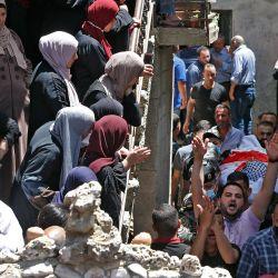 Familiares de Ahmed Daraghmeh, un miembro de los servicios de inteligencia palestinos que fue asesinado por las fuerzas israelíes el día anterior en el cruce de Zaatara al sur de Nablus en la ocupada Cisjordania, miran cómo su cuerpo pasa por debajo durante una procesión funeraria en la ciudad de al-Lubban al-Sharqiya cerca de Nablus.   Foto:Abbas Momani / AFP