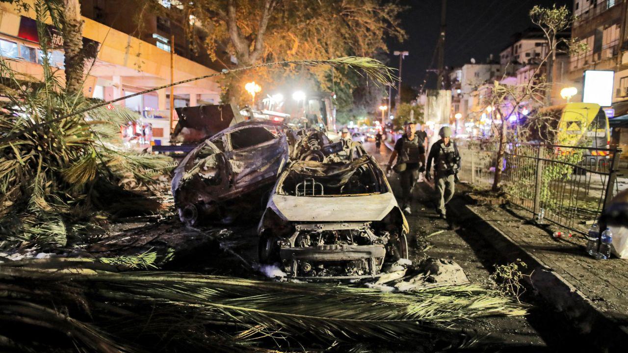 Las fuerzas de seguridad israelíes pasan junto a vehículos quemados extinguidos en Holon, cerca de Tel Aviv, después de que se lanzaran cohetes hacia Israel desde la Franja de Gaza controlada por el movimiento palestino Hamas.   Foto:Ahmad Gharabli / AFP