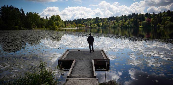En la foto se ve a un hombre parado en un muelle en Deer Lake en Burnaby.