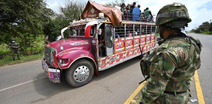 Un autobús pasa junto a los soldados que hacen guardia cerca de una barricada que bloquea la carretera Panamericana luego de una protesta contra el gobierno provocada por un proyecto de reforma tributaria ahora abandonado, en Cali, Colombia.