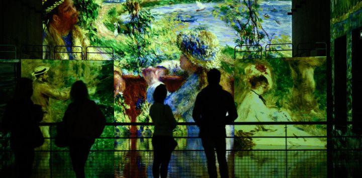 Periodistas observan proyecciones de pinturas durante una visita de prensa de la exposición digital titulada
