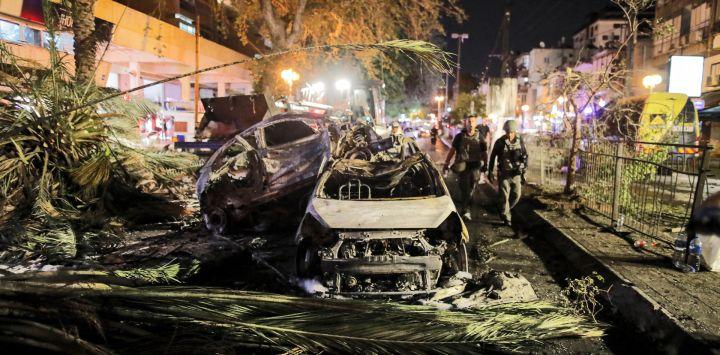 Las fuerzas de seguridad israelíes pasan junto a vehículos quemados extinguidos en Holon, cerca de Tel Aviv, después de que se lanzaran cohetes hacia Israel desde la Franja de Gaza controlada por el movimiento palestino Hamas.