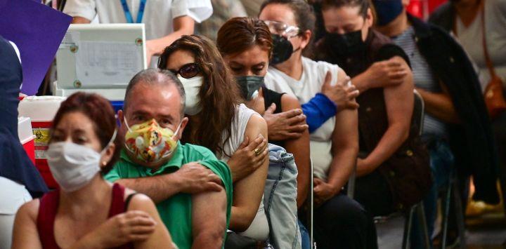 La gente espera luego de recibir dosis de la vacuna Pfizer-BioNTech contra COVID-19 en un centro de vacunación para mayores de 50 años instalado en la Biblioteca Vasconcelos, en la Ciudad de México.