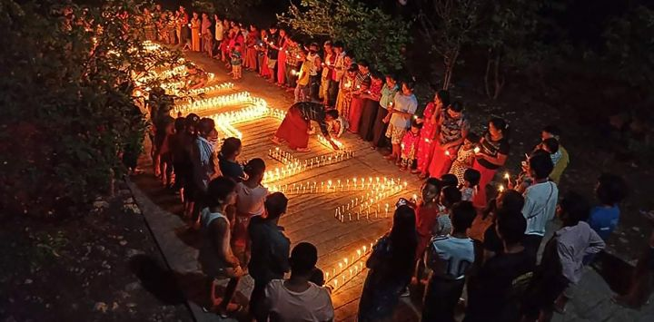Esta foto muestra a personas reunidas durante una protesta nocturna contra el golpe militar, marcando los 100 días de la toma de poder en el municipio de Hpakant en Myanmar Estado norteño de Kachin.