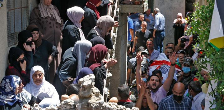 Familiares de Ahmed Daraghmeh, un miembro de los servicios de inteligencia palestinos que fue asesinado por las fuerzas israelíes el día anterior en el cruce de Zaatara al sur de Nablus en la ocupada Cisjordania, miran cómo su cuerpo pasa por debajo durante una procesión funeraria en la ciudad de al-Lubban al-Sharqiya cerca de Nablus.