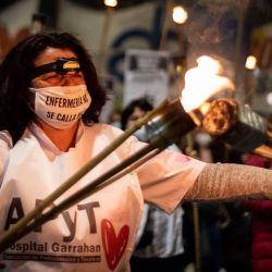 Una enfermera porta antorchas durante una marcha de protesta desde el Congreso Nacional hasta la Plaza de Mayo exigiendo mejores condiciones laborales y recordando a sus compañeros fallecidos por el coronavirus (Covid-19), en el Día Internacional de la Enfermera.   Foto:Julieta Ferrario / ZUMA Wire / DPA