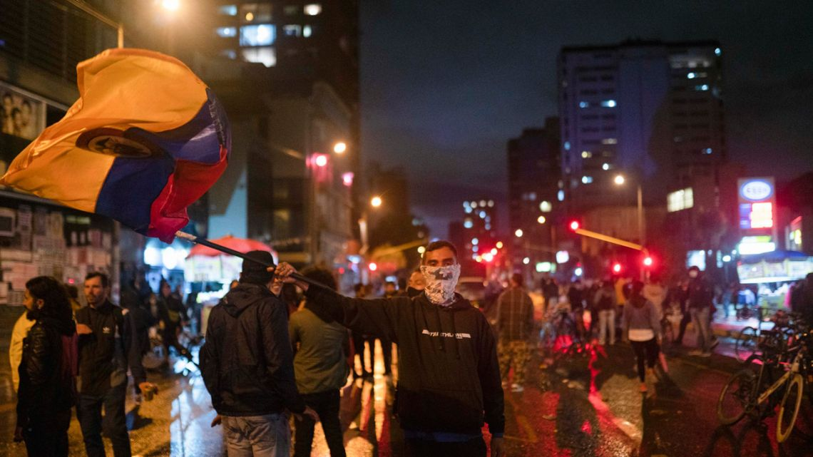 A demonstrator waves the Colombian flag during a protest against the government's tax reforms in Bogotá, Colombia, on Wednesday, May 5, 2021.