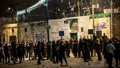 Un grupo de árabes se reúnen frente a una mezquita antes de chocar con manifestantes judíos en la ciudad de Lod.