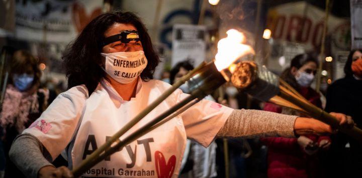 Una enfermera porta antorchas durante una marcha de protesta desde el Congreso Nacional hasta la Plaza de Mayo exigiendo mejores condiciones laborales y recordando a sus compañeros fallecidos por el coronavirus (Covid-19), en el Día Internacional de la Enfermera.