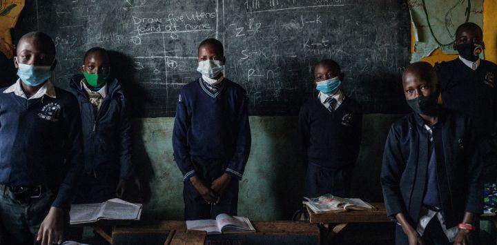 Los estudiantes del Centro para niños Miracle and Victory, una escuela primaria privada para huérfanos, se levantan para saludar a su maestro mientras las escuelas reabren después de un receso de 6 semanas siguiendo la directiva del presidente keniano Uhuru Kenyatta para frenar la propagación del coronavirus Covid-19, en Kibera. tugurio, Nairobi.