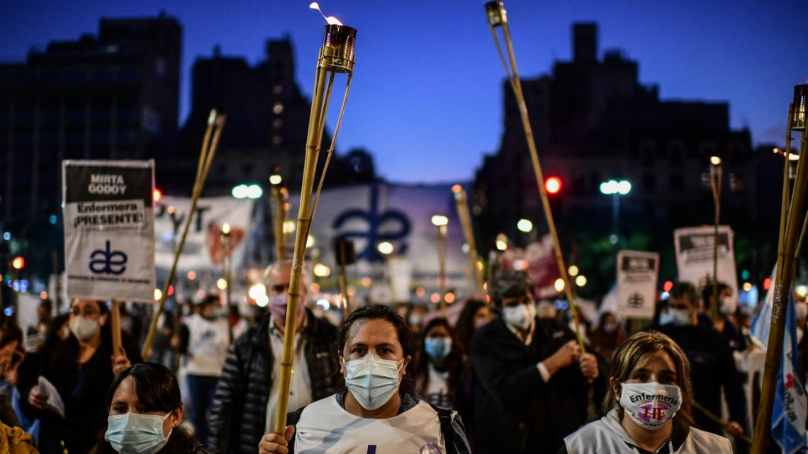 Nurses shout slogans during a protest demanding better salaries, working conditions and equipment during International Nurses day in Buenos Aires, on May 12, 2021.
