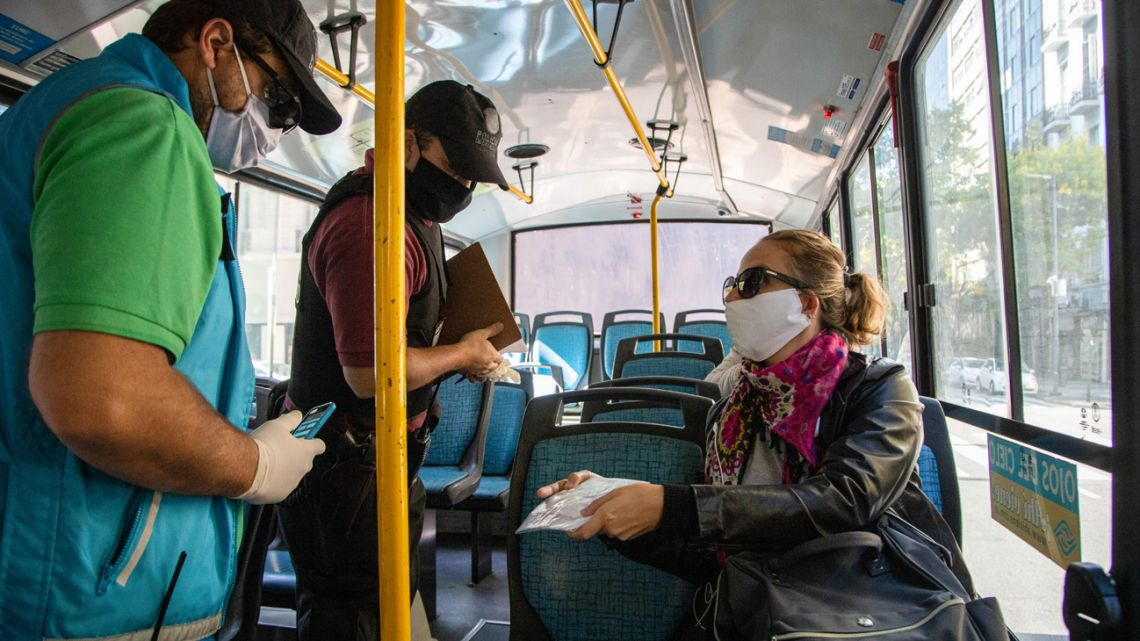 Police check the permission to circulate of a citizen riding on a bus in Buenos Aires.