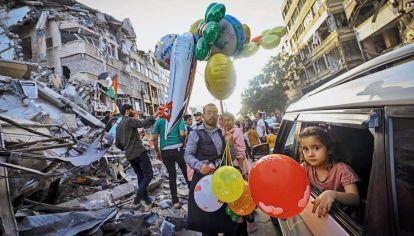 La vida sigue. Un vendedor de globos junto a uno de los edificios destruidos por la aviación israelí en Gaza, donde murieron 66 niños.