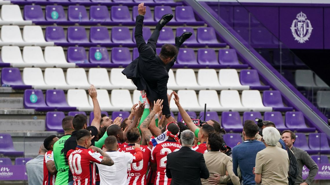 Atlético Madrid's  players toss Argentine coach Diego Simeone after winning the Spanish league football match against Real Valladolid FC and the Liga Championship title at the Jose Zorilla stadium in Valladolid on May 22, 2021. Atletico Madrid´s players toss Atletico Madrid's Argentine coach Diego Simeone after winning the Spanish league football match against Real Valladolid FC and the Liga Championship title at the Jose Zorilla stadium in Valladolid on May 22, 2021.