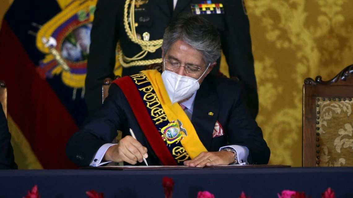 Ecuador's newly sworn-in President Guillermo Lasso signs a document as he presents the members of his cabinet at the Carondelet presidential palace in Quito, on May 24, 2021.