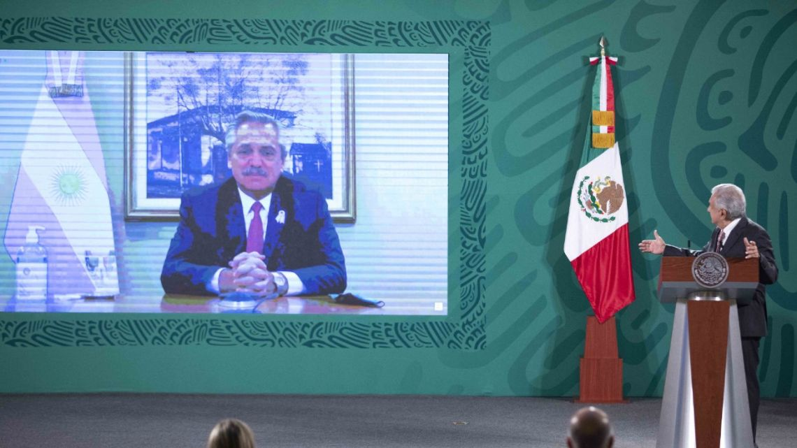 Handout picture released by the Mexican Presidency shows Mexican President Andrés Manuel López Obrador (right) holding a video conference with his Argentine counterpart Alberto Fernández during his daily press conference in Mexico City on May 25, 2021.