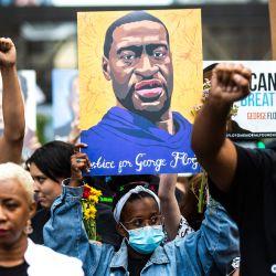 Las personas levantan los puños mientras marchan durante un evento en recuerdo de George Floyd en Minneapolis, Minnesota. | Foto:Kerem Yucel / AFP