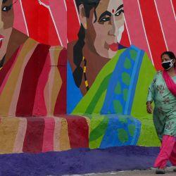 Una mujer camina por una calle pasando un mural que representa a mujeres transgénero para crear conciencia sobre la comunidad transgénero, en Mumbai. | Foto:Punit Paranjpe / AFP