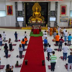 Los devotos rezan junto a una estatua para conmemorar el festival budista del Día de Vesak para conmemorar el nacimiento, la iluminación y la muerte de Buda, en la ciudad de Surabaya en Java Oriental. | Foto:Juni Kriswanto / AFP