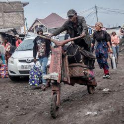 Un hombre lleva equipaje en una bicicleta tradicional de madera para los residentes que huyen de Goma después de que se diera una orden de evacuación de parte de la ciudad por el riesgo de erupción del volcán Nyiragongo, provocando inmediatamente el éxodo de decenas de miles de personas.   Foto:Guerchom Ndebo / AFP