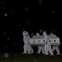 Malasia: El equipo de Tajhiz del Departamento de Asuntos Religiosos Islámicos de Negeri Sembilan (JHEAINS) lleva el ataúd de una víctima de COVID-19 para el entierro por la noche bajo la lluvia en el cementerio Makam Tuan Haji Said. Ayer, Malasia registró el mayor número de casos con 7.478 casos positivos y 63 muertes.   Foto:Izzul Ahmad (STR) / BERNAMA / DPA