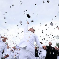 Los cadetes que se gradúan lanzan sus sombreros al aire en la conclusión de la ceremonia de graduación y puesta en servicio de la Academia Naval de los EE. UU.   Foto:Kevin Dietsch / Getty Images / AFP
