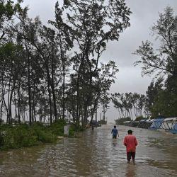 Los aldeanos caminan por el agua en una carretera inundada para llegar a un refugio mientras el ciclón Yaas avanza hacia la costa este de la India en la Bahía de Bengala, en Digha, a unos 190 km de Calcuta.   Foto:Dibyangshu Sarkar / AFP
