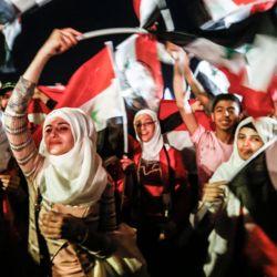 Los sirios que ondean banderas nacionales celebran en las calles de la capital Damasco, un día después de una elección programada para darle al actual presidente Bashar al-Assad un cuarto mandato.   Foto:Louai Beshara / AFP