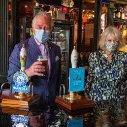 El príncipe Carlos de Gales, Príncipe de Gales de Gran Bretaña se prepara para tomar una pinta de cerveza 'Wandle' de la cervecería Sambrook mientras la duquesa de Cornualles Camilla de Gran Bretaña observa durante su visita al pub Prince of Wales en Clapham Old Town, al sur de Londres. | Foto:Heathcliff O'Malley / POOL / AFP