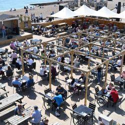Los comensales disfrutan del clima en un restaurante al aire libre junto a la playa de Brighton, en el sur de Inglaterra, a medida que aumentan las temperaturas en todo el país.   Foto:Glyn Kirk / AFP