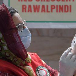 Un trabajador de la salud se prepara para inocular a una mujer con una dosis de la vacuna Sinovac del coronavirus Covid-19 en el centro de vacunación de la Media Luna Roja en Rawalpindi. | Foto:Farooq Naeem / AFP