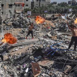 Los miembros palestinos del equipo deportivo Bar Woolf de Gaza actúan con fuego sobre las ruinas de un edificio destruido en los recientes ataques aéreos israelíes, en Beit Lahia.   Foto:Mahmud Hams / AFP