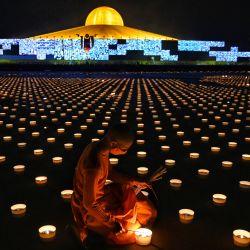 Un monje budista enciende velas para conmemorar el Día de Visakha Bucha o el Día de Vesak, una celebración del nacimiento, la iluminación y la muerte del Señor Buda que se lleva a cabo en la luna llena del tercer mes lunar del calendario budista, en el templo budista Wat Dhammakaya en las afueras. de Bangkok.   Foto:Lillian Suwanrumpha / AFP
