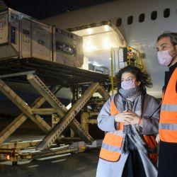 Santiago Cafiero y la ministra de Salud, Carla Vizzotti, posando mientras se descargan contenedores con unas 2.148.600 vacunas Oxford / AstraZeneca COVID-19 a su llegada desde los EE. UU., en el aeropuerto internacional de Ezeiza.   Foto:Maria Eugenia Cerutti / Presidencia Argentina / AFP