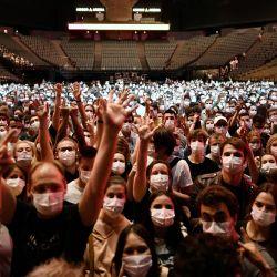 La gente levanta la mano antes del inicio de un concierto de prueba de la banda de rock francesa Indochine y el DJ francés Etienne de Crecy, cuyo objetivo es investigar cómo estos eventos pueden tener lugar de manera segura en medio de la pandemia de Covid-19 en el AccorHotels Arena en París.   Foto:Stephane De Sakutin / AFP