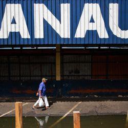 Un hombre camina por una calle inundada en Manaos, estado de Amazonas, Brasil. | Foto:Michael Dantas / AFP