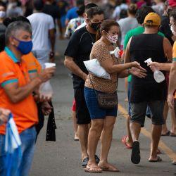 Los empleados ofrecen desinfectante a los visitantes en el cementerio de Nossa Senhora Aparecida, en Manaos, estado de Amazonas, Brasil, en medio de la pandemia del nuevo coronavirus COVID-19. | Foto:Michael Dantas / AFP