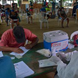 Un residente con síntomas de COVID-19 llena un formulario para recibir asistencia médica de miembros de la Organización Internacional para las Migraciones (OIM), mientras otros esperan su turno, en la comunidad ribereña de Bela Vista do Jaraqui, Manaos, estado de Amazonas, Brasil. | Foto:Marcio James / AFP