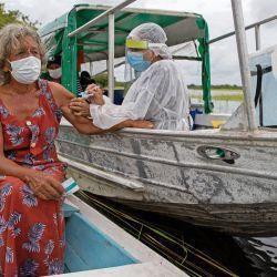 Olga D'arc Pimentel, de 72 años, es vacunada por un trabajador de la salud con una dosis de la vacuna COVID-19 Oxford-AstraZeneca en la comunidad de Nossa Senhora Livramento a orillas del Río Negro cerca de Manaus, estado de Amazonas, Brasil. | Foto:Michael Dantas / AFP
