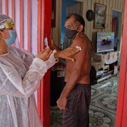 Joao Aquino Filho es vacunado por un trabajador de la salud con una dosis de la vacuna COVID-19 Oxford-AstraZeneca en la comunidad de Nossa Senhora Livramento en las orillas del Río Negro cerca de Manaos, estado de Amazonas, Brasil. | Foto:Michael Dantas / AFP