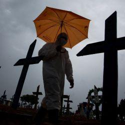 Un trabajador vestido con un traje protector y con un paraguas camina frente a las tumbas de las víctimas del COVID-19 en el cementerio de Nossa Senhora Aparecida, en Manaos, Brasil. | Foto:Michael Dantas / AFP
