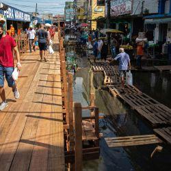 La gente camina por una pasarela de madera construida para cruzar calles inundadas en Manaos, estado de Amazonas, Brasil. | Foto:Michael Dantas / AFP