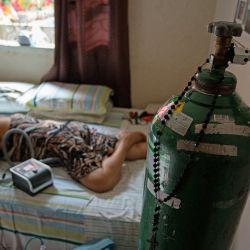Dilza Maria Pereira Rodrigues, de 71 años, recibe tratamiento por COVID-19 en su casa después de 15 días de tratamiento en el hospital de Manaus, Brasil. | Foto:Michael Dantas / AFP