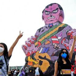 Un manifestante muestra el letrero V mientras otros levantan los puños cerrados durante una protesta contra el manejo del presidente brasileño Jair Bolsonaro de la pandemia de COVID-19 cerca de una muñeca inflable gigante que lo representa como un monstruo, en Brasilia. | Foto:Evaristo Sa / AFP