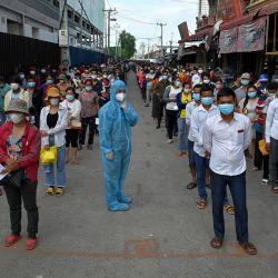 Un funcionario en equipo de protección personal (EPP) maneja a la multitud mientras la gente hace cola para recibir la vacuna contra el coronavirus Sinopharm Covid-19 de China en Phnom Penh, como parte de la campaña del gobierno para detener el creciente número de casos del virus. | Foto:Tang Chhin Sothy / AFP