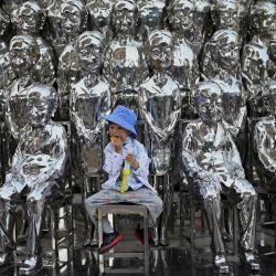 Un niño se sienta en una silla entre esculturas que se exhiben en un centro comercial en el Día Internacional del Niño en Beijing, un día después de que China anunciara que permitiría a las parejas tener tres hijos. | Foto:Noel Celis / AFP