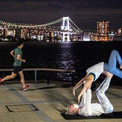 Un corredor pasa corriendo junto a personas que practican yoga en un parque en el área de la bahía de Tokio. | Foto:Charly Triballeau / AFP