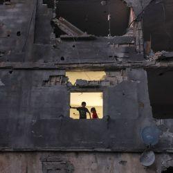 Los niños palestinos se paran en la ventana de su casa en un edificio gravemente dañado durante los recientes ataques israelíes, en Beit Hanun, en el norte de la Franja de Gaza, más de una semana después de que un alto el fuego puso fin a 11 días de hostilidades entre Israel y Gaza gobiernan Hamas. | Foto:Mahmud Hams / AFP